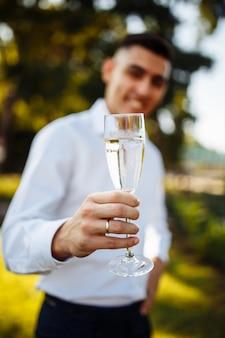 Copos com champanhe na mão de uma jovem bonita.