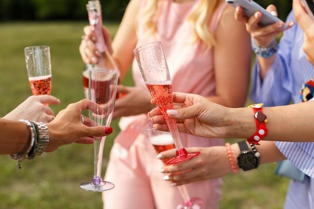Copos com champanhe nas mãos. piquenique da mulher no parque de domingo.