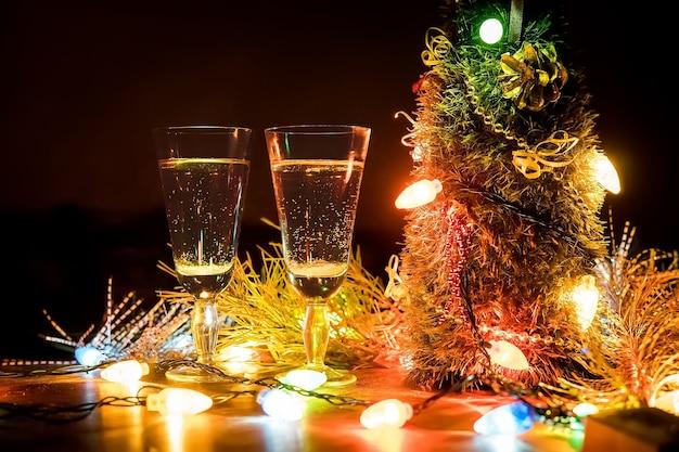 Copos com champanhe no contexto de uma guirlanda. plano de fundo dia dos namorados. a celebração do natal e ano novo casais apaixonados