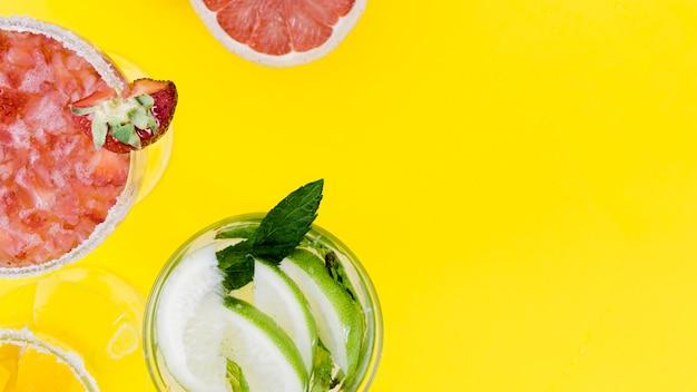 Copos com cocktails de morango e limão em fundo amarelo