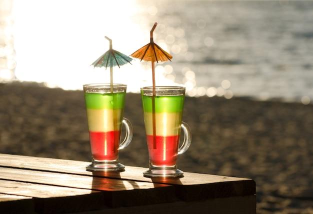 Copos com coquetéis multicoloridos em uma mesa de madeira no sol, na praia e no mar
