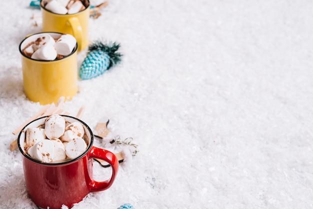 Copos com doces doces perto de brinquedos de natal entre a neve