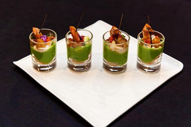 Copos com petiscos de frutos do mar e massas verdes em bandeja de banquete para eventos e buffet. catering, petiscos de camarão para um banquete.