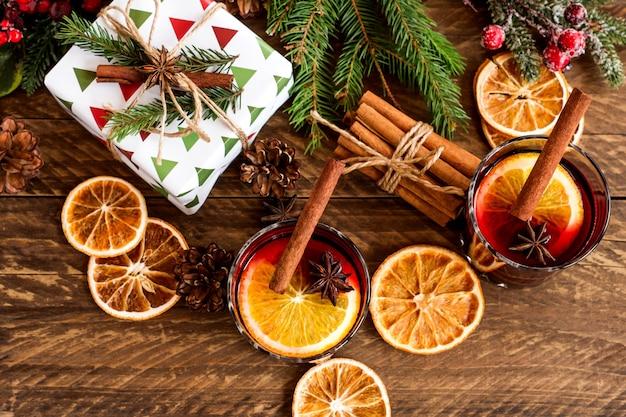 Copos com quente vermelho quente para o inverno e o natal com uma fatia de laranja, anis e canela em pau decorado com ramos de pinheiro e presentes embrulhados para as festas. cartão festivo.