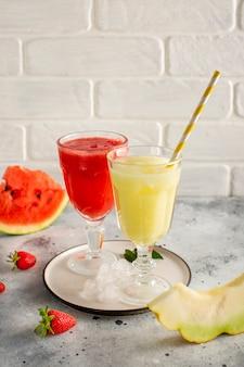 Copos com suco de melancia vermelho e amarelo