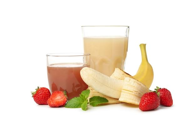 Copos com suco de morango e banana isolados no branco