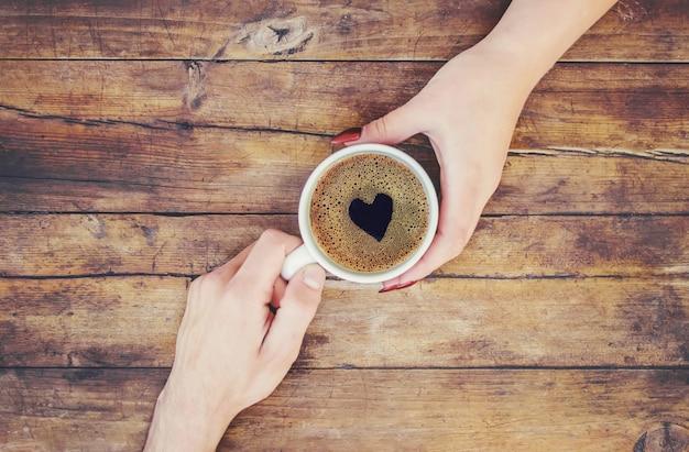 Copos com um café nas mãos de homens e mulheres. foco seletivo.