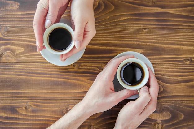 Copos com um café nas mãos de homens e mulheres.