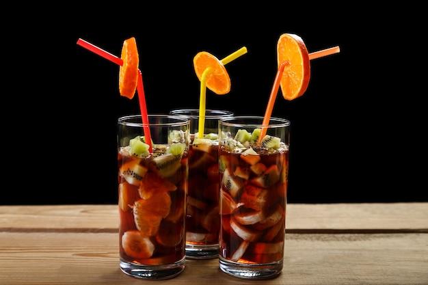 Copos com um coquetel de frutas sobre uma mesa de madeira