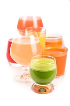 Copos com vegetais orgânicos frescos e sucos de frutas isolados no branco.