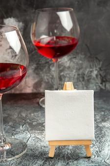 Copos com vista frontal de tela branca vinho em cavalete de madeira no escuro