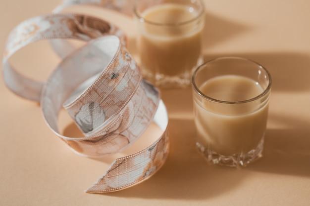 Copos curtos de licor de creme irlandês ou licor de café com fita em um fundo bege claro