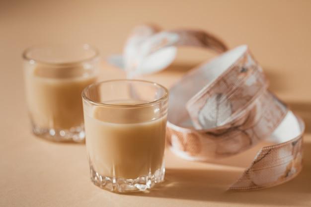 Copos curtos de licor irlandês cremoso ou licor de café com fita em um fundo bege claro