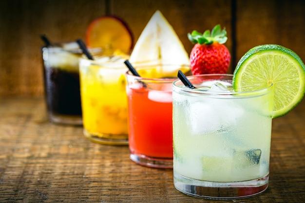 Copos da típica bebida brasileira chamada caipirinha, nos sabores de maracujá, limão, morango, ameixa e melancia
