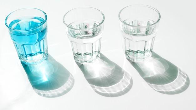 Copos de água azul com sombra no pano de fundo branco