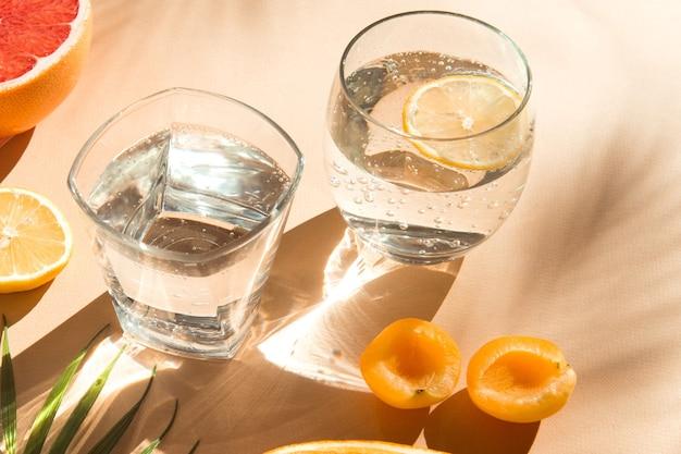 Copos de água com frutas na luz do sol fechem o verão fresco e saudável bebidas cor bege backgrou