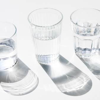 Copos de água com sombra escura no fundo branco