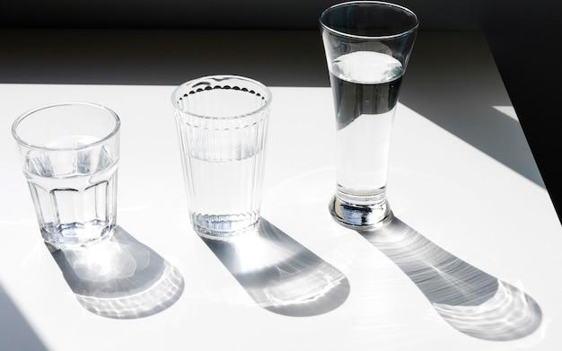Copos de água com sombra no pano de fundo branco