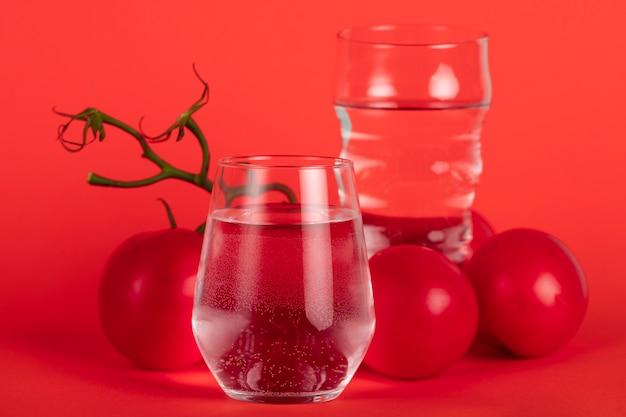 Copos de água e arranjo de tomates