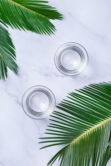 Copos de água em um fundo de mármore da moda com folhas de palmeira verdes. beleza natural e saúde, conceito anti-envelhecimento de cuidados com a pele de bem-estar. vista superior, configuração plana, espaço de cópia