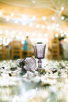 Copos de água no chão com luzes e mesas no fundo. vista lateral.