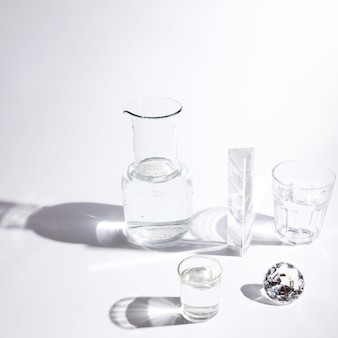 Copos de água; prisma; diamante cintilante e copo com sombra no fundo branco