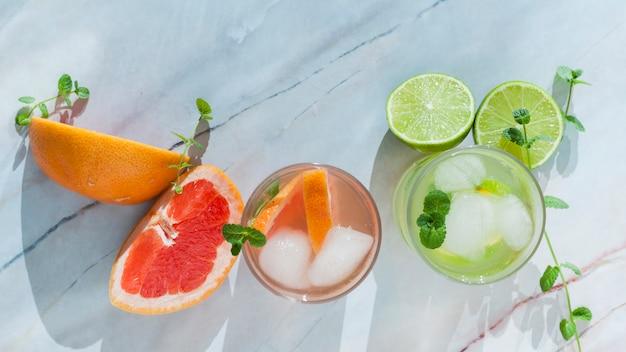 Copos de bebida cítrica com frutas fatiadas