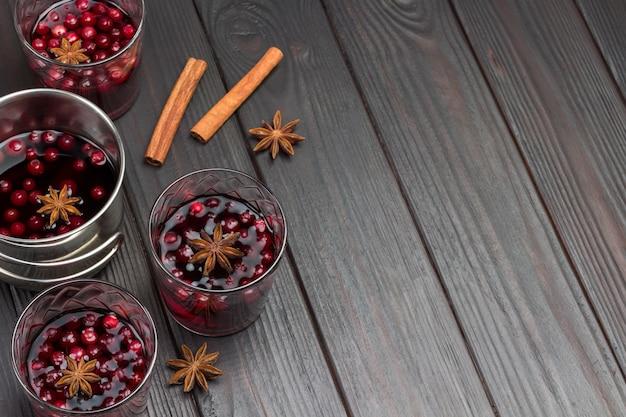 Copos de bebida com cranberries e especiarias. paus de canela na mesa. vista do topo. copie o espaço