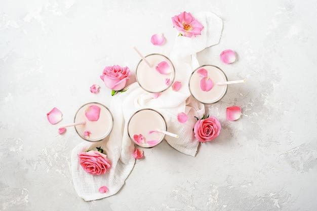 Copos de bebida de leite de lua com rosas em um fundo de concreto. vista do topo.
