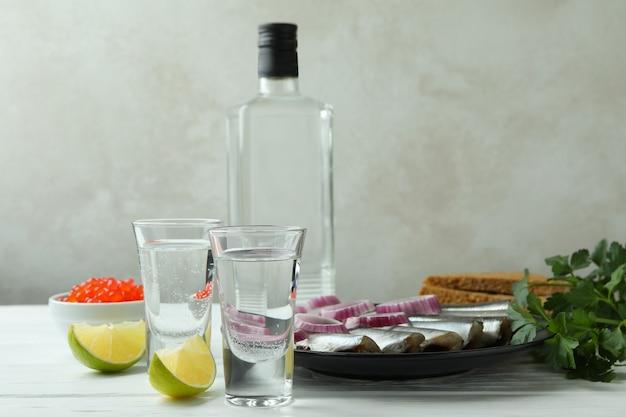 Copos de bebida e petiscos saborosos na mesa de madeira branca