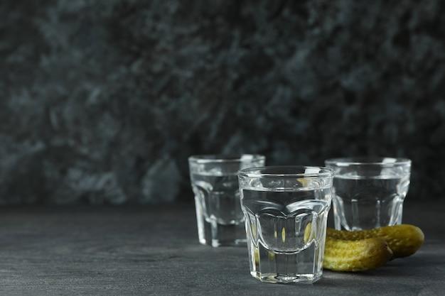 Copos de bebida e petiscos saborosos na mesa de madeira escura