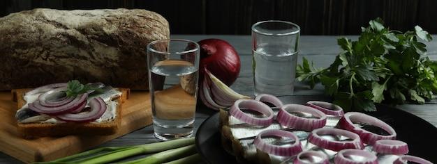 Copos de bebida e petiscos saborosos na mesa de madeira