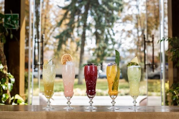 Copos de bebida não alcoólica e frutas sobre uma mesa com um fundo desfocado.