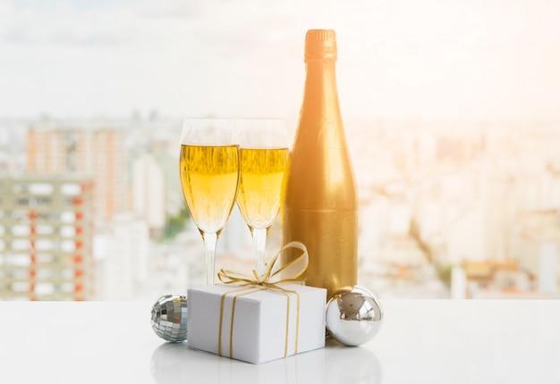 Copos de bebida perto de caixa de presente e garrafa