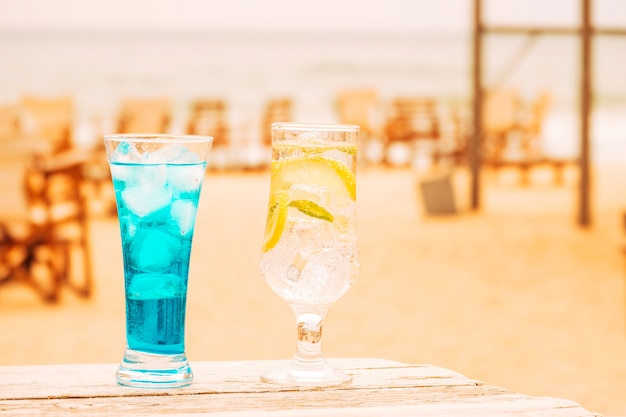 Copos de bebidas frescas de hortelã azul na mesa de madeira