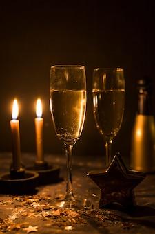 Copos de bebidas perto de enfeite estrela e velas