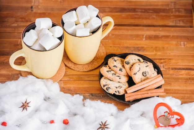 Copos de cacau com marshmallows e prato com biscoitos
