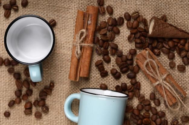 Copos de café azuis vazios, paus de canela e feijão em uma serapilheira. vista do topo.