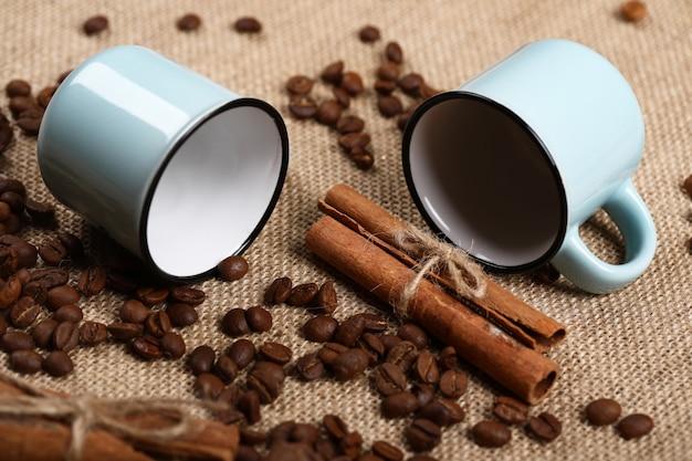 Copos de café azuis vazios, paus de canela e feijão em uma serapilheira.
