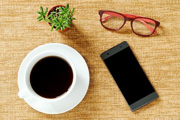 Copos de café da vista superior, telefones espertos, árvores verdes pequenas e vidros em um fundo marrom.