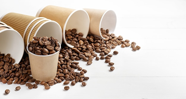 Copos de café de papel com grãos de café na mesa branca