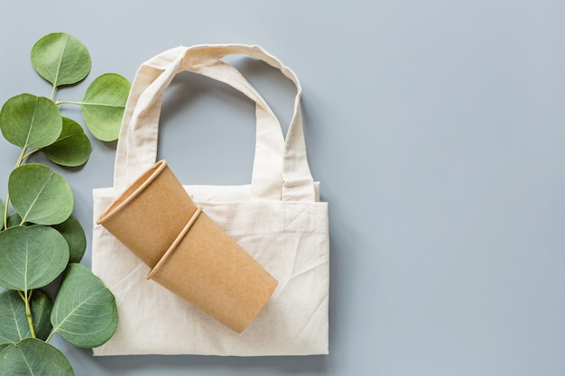 Copos de café de papel natural eco e sacola de compras plana leigos sobre fundo cinza. conceito de estilo de vida sustentável.