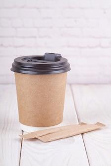 Copos de café de papel ofício em uma mesa branca perto do fundo da parede de luz