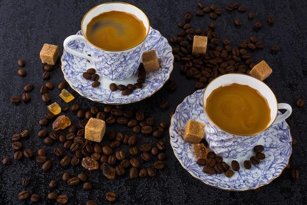 Copos de café e grãos de café na superfície preta