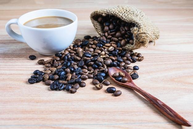 Copos de café e grãos de café torrados em uma mesa de madeira