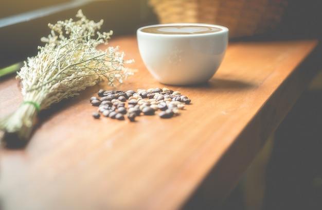 Copos de café, feijões de café e flores secadas em uma tabela de madeira. esta imagem é foco borrado e macio.