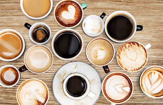 Copos de café variados em uma mesa de madeira