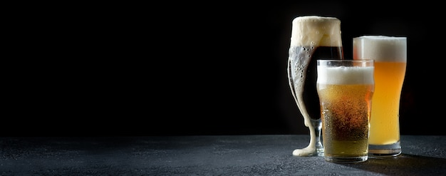 Copos de cerveja clara, escura e trigo em um fundo escuro