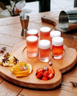 Copos de cerveja com espuma e frutas fatiadas no quadro