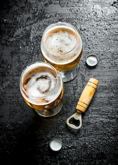 Copos de cerveja e abridor. na superfície rústica preta